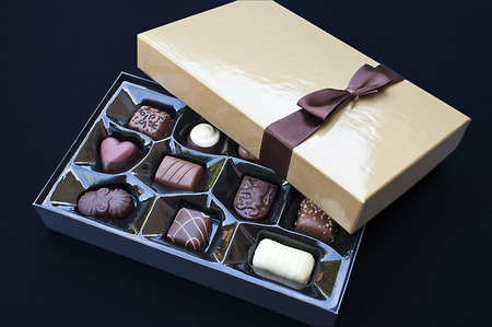 Open golden chocolate box with a brown ribbon Stock Photo