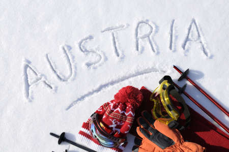 The word Austria written in snow with ski poles, goggles and hats. photo