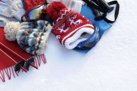 bobble: Winter sports background with ski poles, goggles, hats and gloves with copyspace (picture taken in fresh snow with directional winter sun). Stock Photo