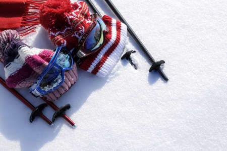 Winter snow sports background with ski poles, goggles, hats and gloves with copyspace . photo
