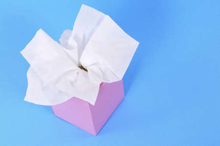 Tissues: Paper tissues in blank pink box on a blue background.