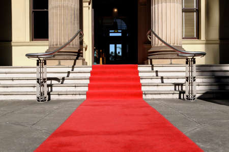 Red carpet laid in front entrance of a luxury hotel building photo