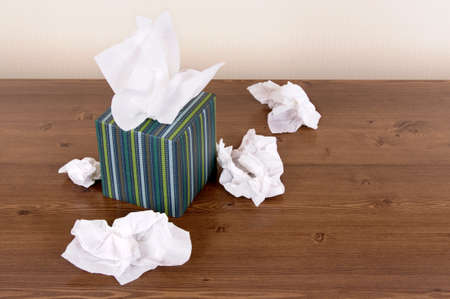 Tissues: Box of tissue style tissues on a wood table. Stock Photo