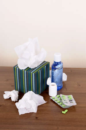 Tissues: Box of tissues and medicine on a wood table.