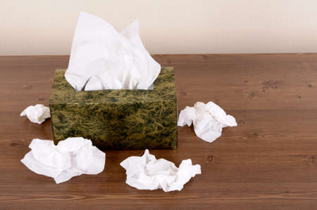 Tissues: Box of tissues on a wood table . Stock Photo