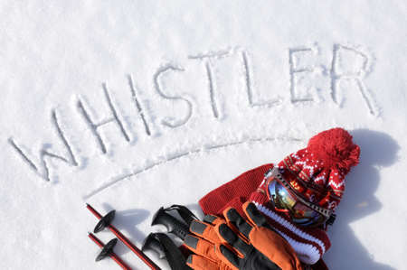 whistler: The word Whistler written in snow with ski poles, goggles and hats.