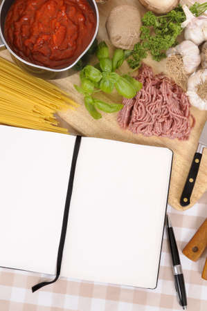 Making Italian spaghetti bolognese with ingredients and blank recipe book or cookbook. Space for copy.