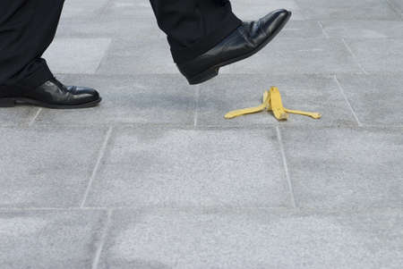 banana skin: Businessman about to step on a banana skin