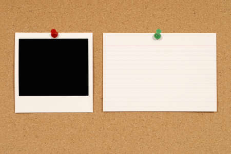Cork notice or bulletin board with blank instant camera photo print and white office index card. Space for copy. photo