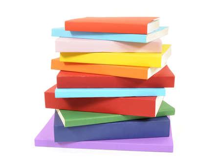 Rommelige stapel of stapel kleurrijke paperback boeken geïsoleerd op een witte achtergrond. Ruimte voor exemplaar.