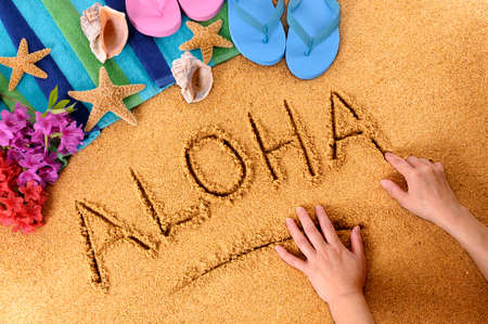 hawaiian lei: Child writing the word Aloha on a sandy beach, with flowers, beach towel, starfish and flip flops. Stock Photo