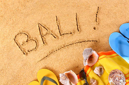 Beach background with towel and flip flops and the word Bali written in sand. Banco de Imagens