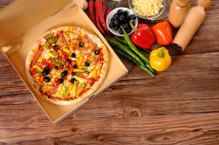 worktop: Freshly baked Pizza in a delivery box surrounded by various ingredients on a wood table or worktop. Stock Photo