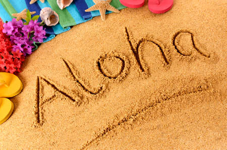 The word Aloha written on a sandy beach, with flowers, beach towel, starfish and flip flops.