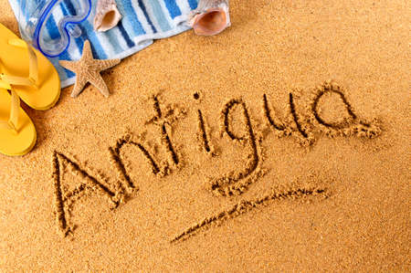 antigua: The word Antigua written on a sandy beach, with scuba mask, beach towel, starfish and flip flops (studio shot - warm color and directional light are intentional).