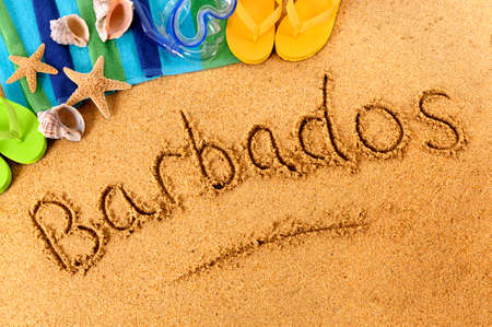 scuba mask: The word Barbados written on a sandy beach, with scuba mask, beach towel, starfish and flip flops. Stock Photo