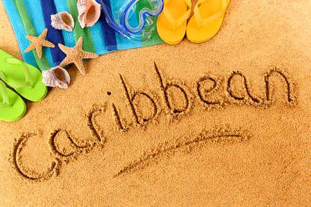 The word Caribbean written on a sandy beach, with scuba mask, beach towel, starfish and flip flops. photo
