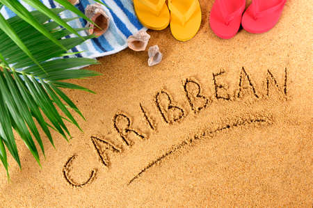 Caribbean beach background with towel, seashells, palm leaves and flip flops. photo