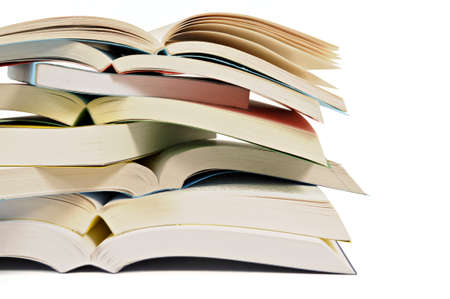 Untidy stack or pile of open paperback books isolated on a white background.  Space for copy. photo