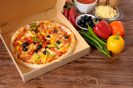 Freshly baked Pizza in a delivery box surrounded by various ingredients on a wood table or worktop. Stock Photo