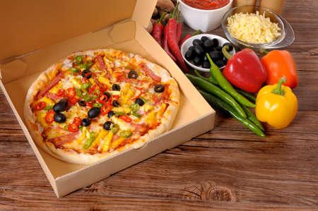 Recién horneado pizza en un cuadro de entrega rodeado de varios ingredientes en una mesa de madera o encimera.
