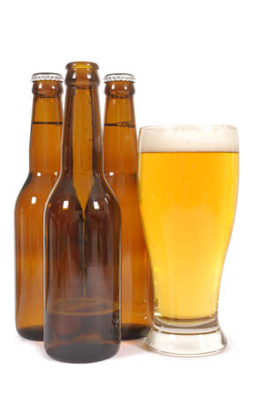 pilsener: Glass of beer with brown bottles one half empty