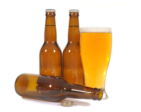 pilsener: Glass of beer with untidy cluster of brown bottles