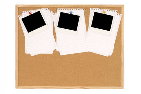 Cork notice or bulletin board with blank instant camera photo prints and several sheets of untidy torn notepaper. Space for copy. photo
