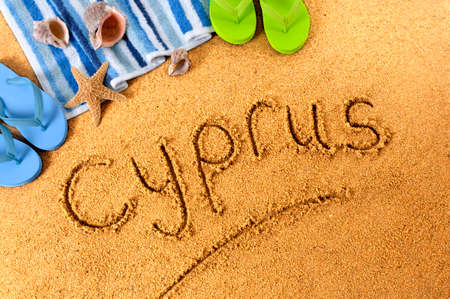 The word Cyprus written on a sandy beach, with beach towel, starfish and flip flops. Archivio Fotografico