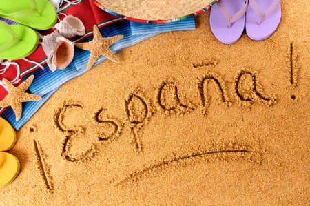 The word Espana (Spain) written on a sandy beach, with sombrero, starfish and flip flops. photo