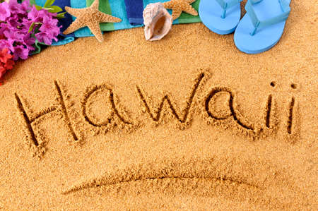 The word Hawaii written on a sandy beach, with flowers, beach towel, starfish and flip flops. Banco de Imagens