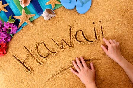 Child writing the word Hawaii on a sandy beach, with flowers, beach towel, starfish and flip flops. photo
