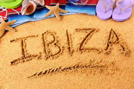 The word Ibiza written on a sandy beach, with  starfish and flip flops.