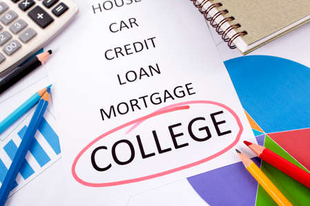 college fund savings: The word College circled in red with a list of saving and debt obligations surrounded by graphs, charts, books and pencils.