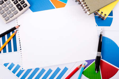 Blank notebook paper surrounded by various charts and graphs, pencils, books and calculator.  Space for copy. photo