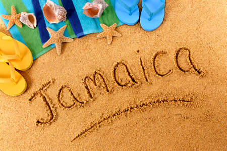 beach towel: The word Jamaica written on a sandy beach, with seashells, beach towel, starfish and flip flops. Stock Photo