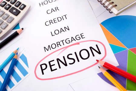The word Pension circled in red with a list of saving and debt obligations surrounded by graphs, charts, books and pencils. photo