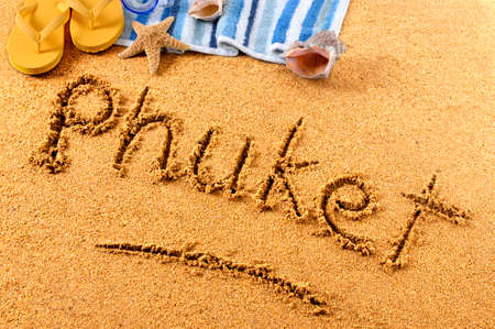 scuba mask: The word Phuket written on a sandy beach, with scuba mask, beach towel, starfish and flip flops. Stock Photo