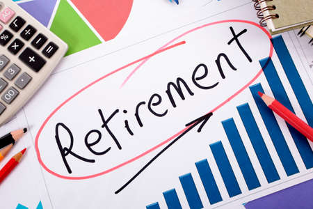 The word Retirement written on a bar graph surrounded by pencils, books and calculator. photo
