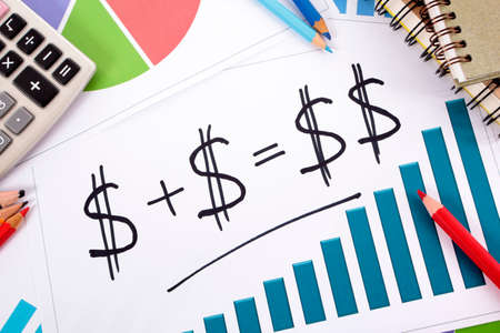 mutual fund: Simple savings or retirement formula on bar graph surrounded by calculator, books and pencils. Stock Photo
