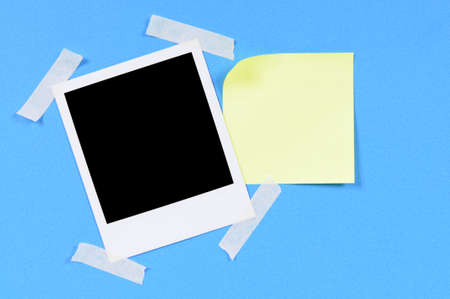 taped: Blank photo print with yellow sticky note taped to blue paper Stock Photo