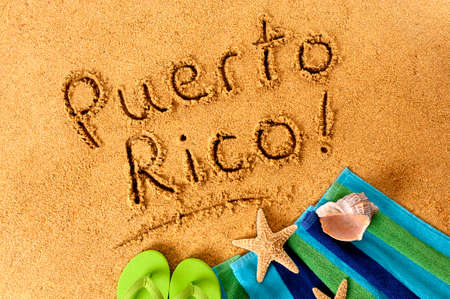 The words Puerto Rico written on a sandy beach, with beach towel, starfish and flip flops.