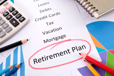 The words Retirement Plan circled in red with a list of saving and debt obligations surrounded by graphs, charts, books and pencils. photo