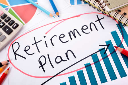 The words Retirement Plan written on a bar graph surrounded by pencils, books and calculator. photo