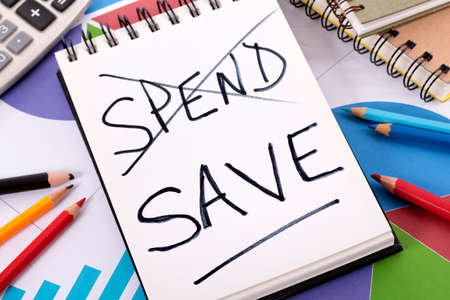 The words spend and save written on a notepad surrounded by pencils, graphs, books and calculator. photo