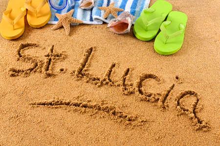 st lucia: The words St Lucia written on a sandy beach, with scuba mask, beach towel, starfish and flip flops.