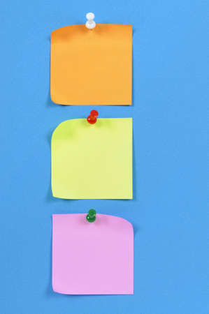 pinned: Office sticky notes pinned to blue paper. Stock Photo