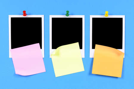 Blank photo prints with sticky notes pinned to blue craft paper.