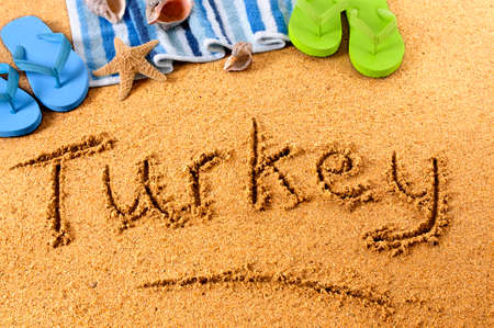 The word Turkey written on a sandy beach, with beach towel, starfish and flip flops. photo