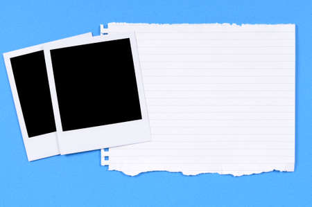 white polaroids: Blank photo prints with torn writing paper against a blue background. Stock Photo